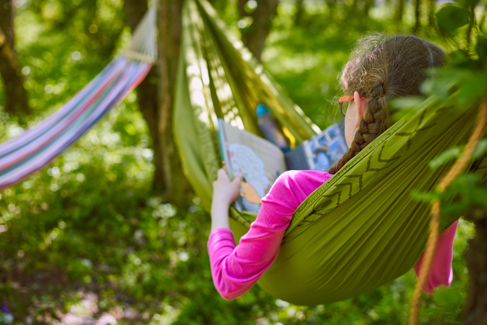 A girl in a hammock reading a book in the woods.