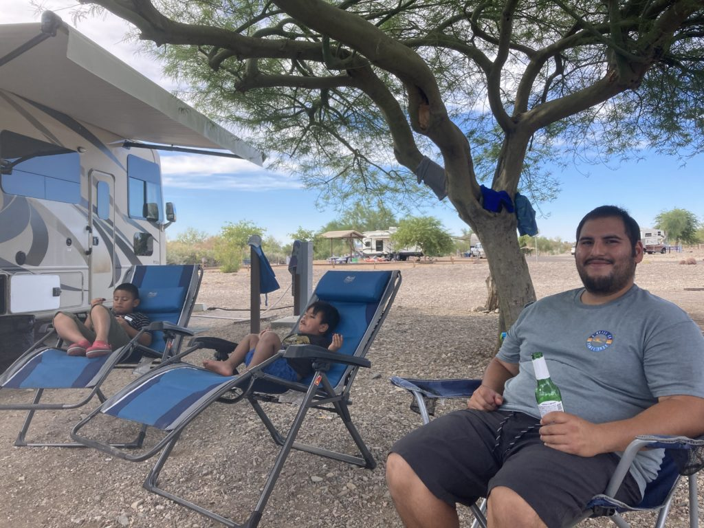 Father sits with two young sons outside a Class A RV