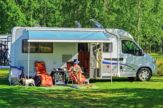 woman relaxing outside an RV under an awning