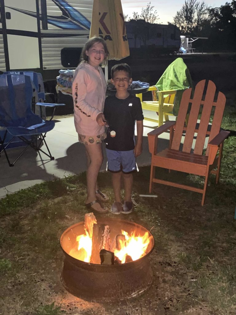 Young boy and girl stand by campfire