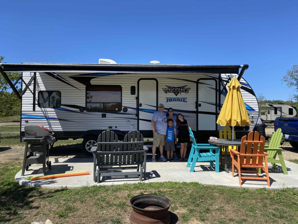 Family of four - mom, dad, son, and daughter - stand outside under the awning of an RV. in the foreground is a table, chairs and umbrella.