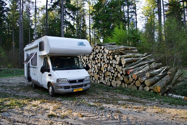 a camper set up next to a large woodpile