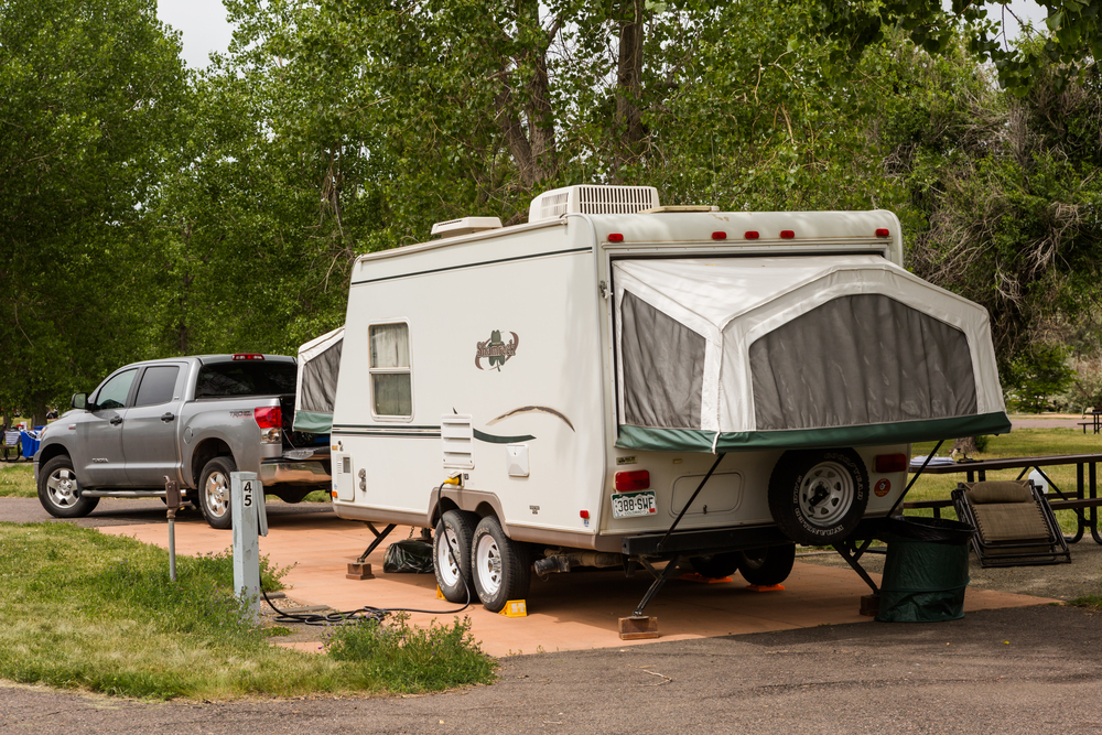 hybrid RV hitched to pick up truck parked at campsite