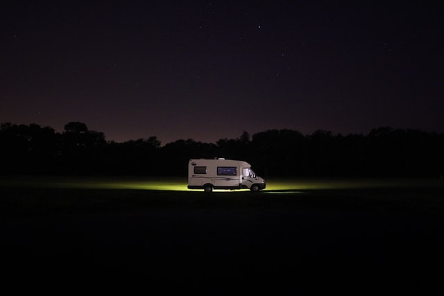 camper driving down a dark road at night