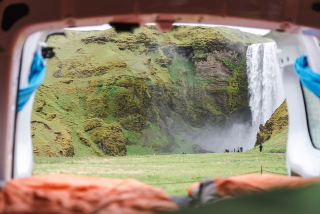 looking out the back of a campervan at a waterfall