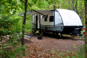 travel trailer parked in the woods