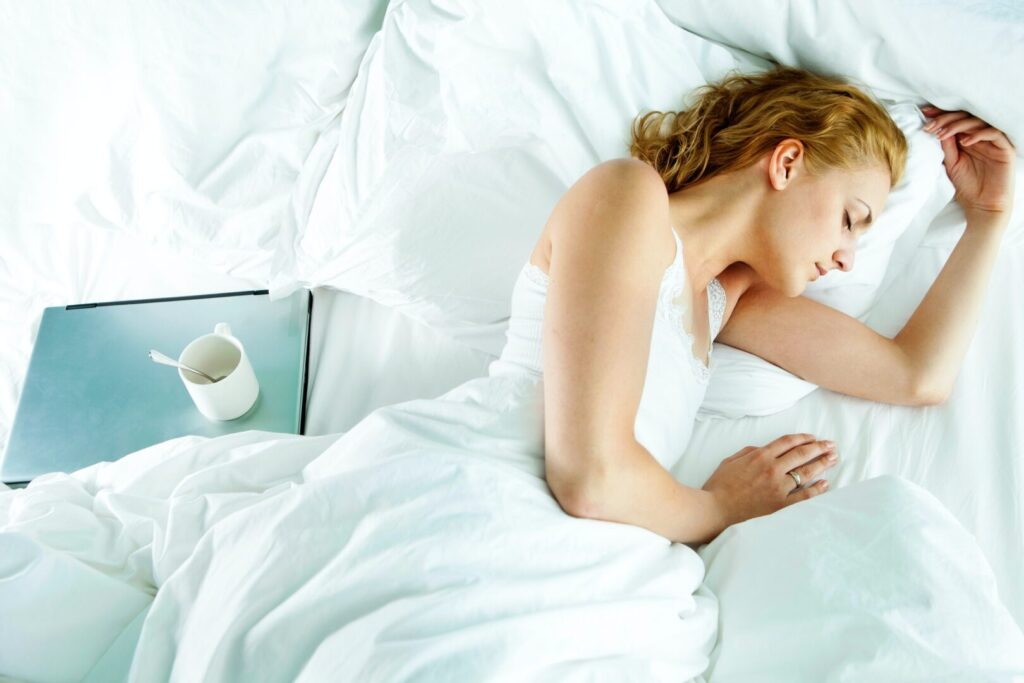 woman resting in bed with a cup of coffee