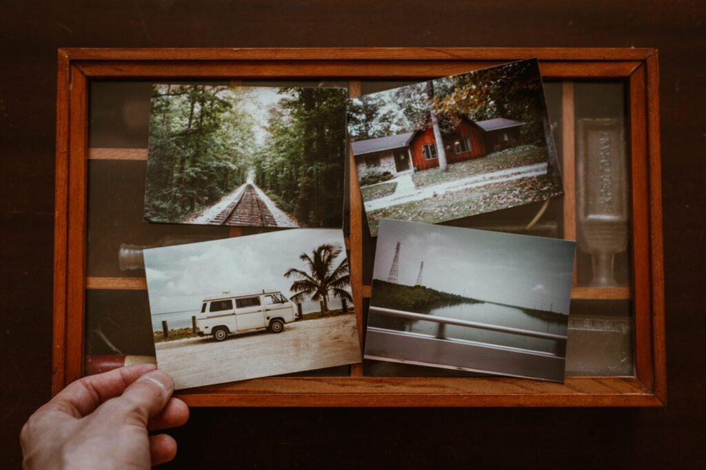 Collage of printed photos: an empty train track, a house, a camper van, and a lake