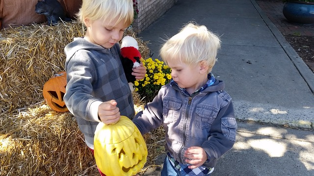 little boys holding pumpkins
