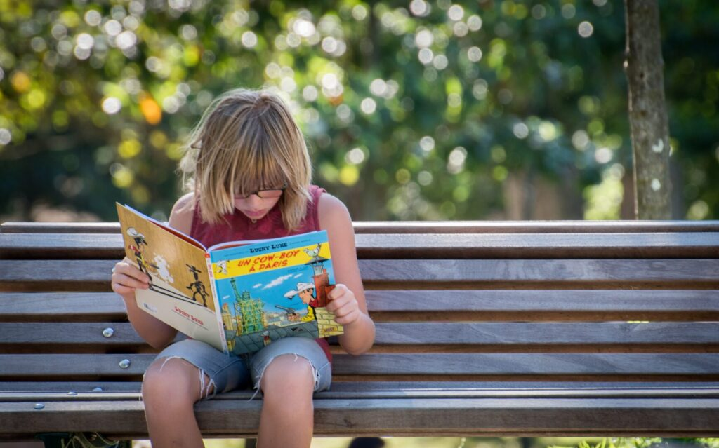 Kid reading a book outdoors