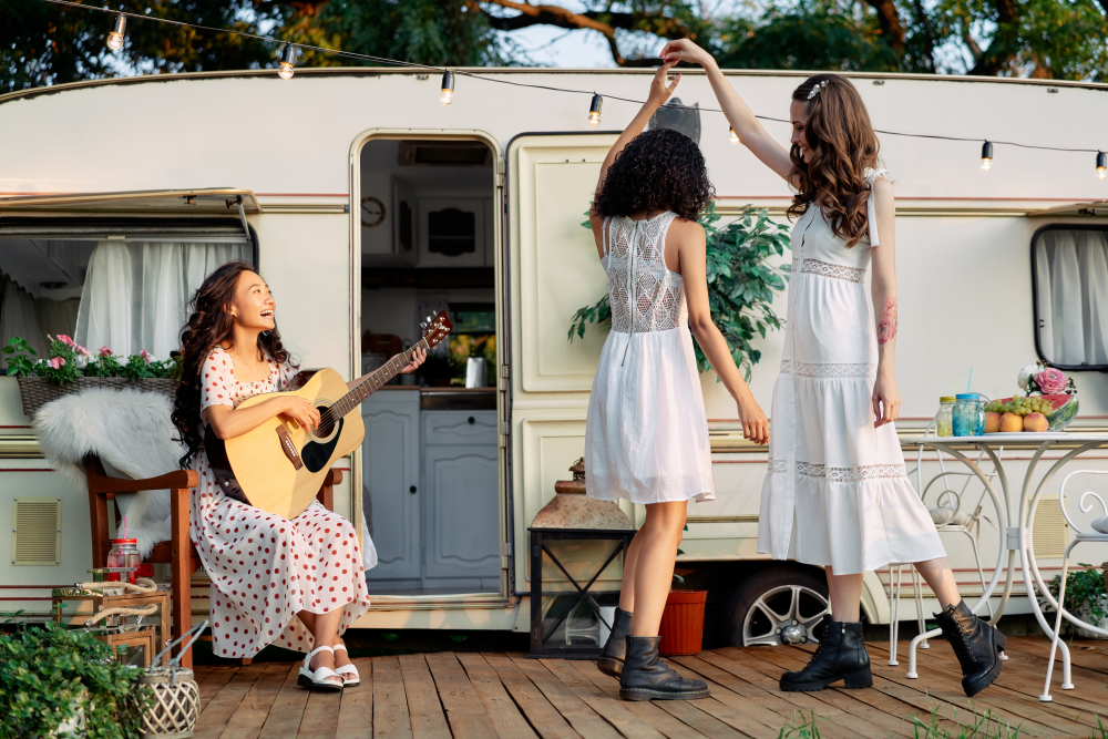 Young happy women have fun together playing guitar and dancing outdoors near their camper van during summer vacation