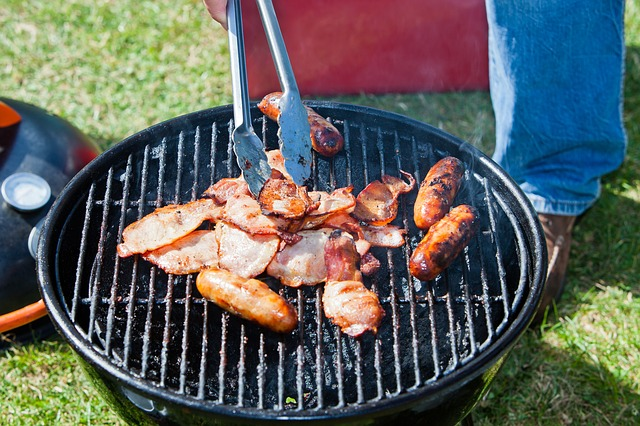 person grilling chicken on a barbeque