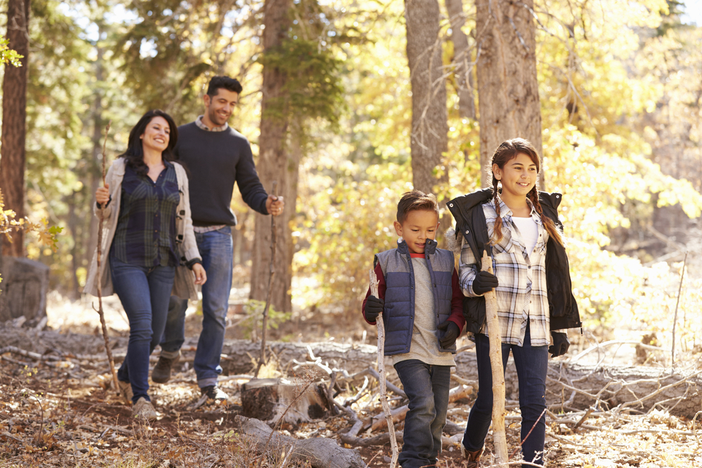 Close up of happy Hispanic family hiking in forest, close up