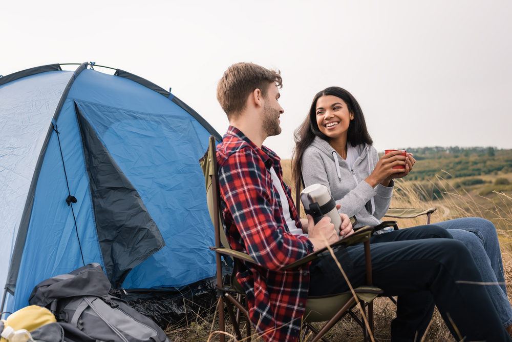 Smiling interracial couple smiling while holding cup and thermos near tent on lawn