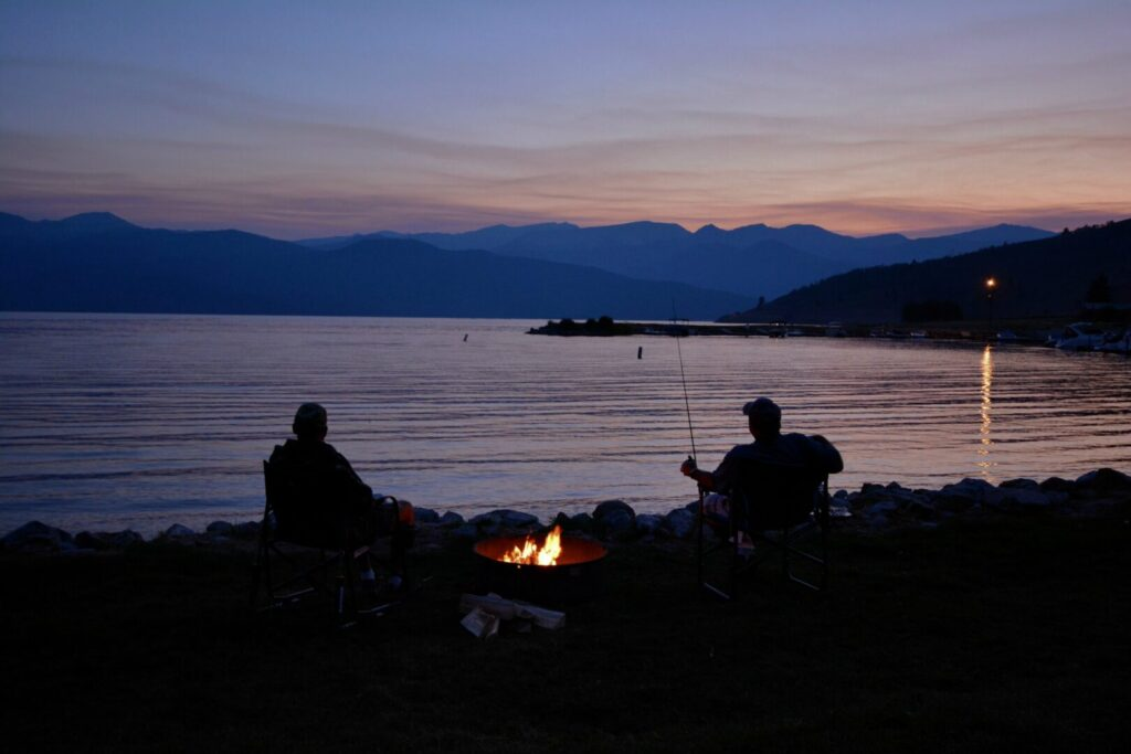 Two men seated at opposite ends of the fire with their fishing poles looking over the lake at sunset