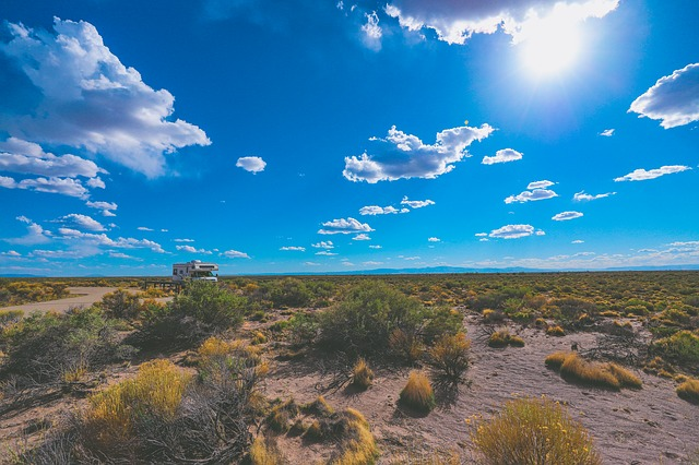 an RV set up under a blue sky and vast desert