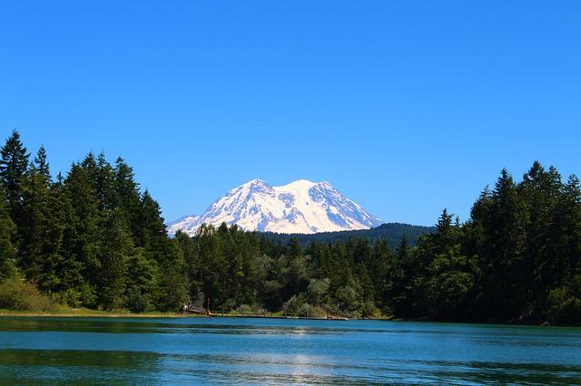 Mount Rainier seen across a clear blue lake