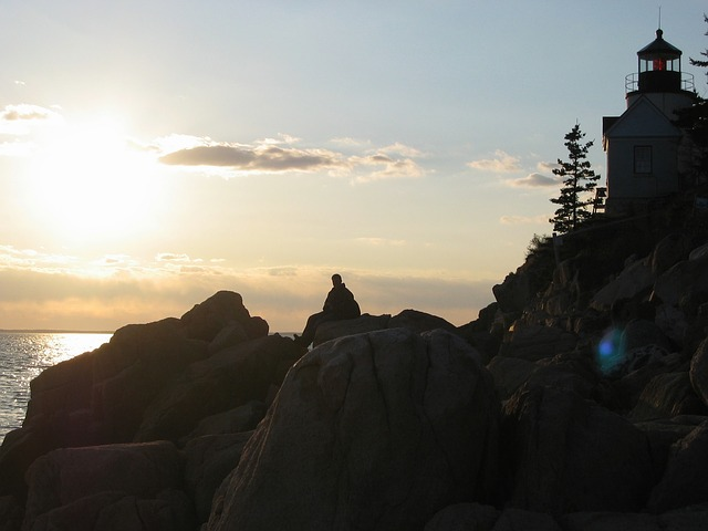 Acadia National Park at sunset with a lighthouse silhouetted