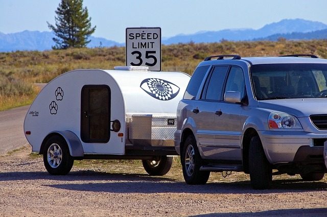 a small SUV towing a teardrop trailer on a desert road