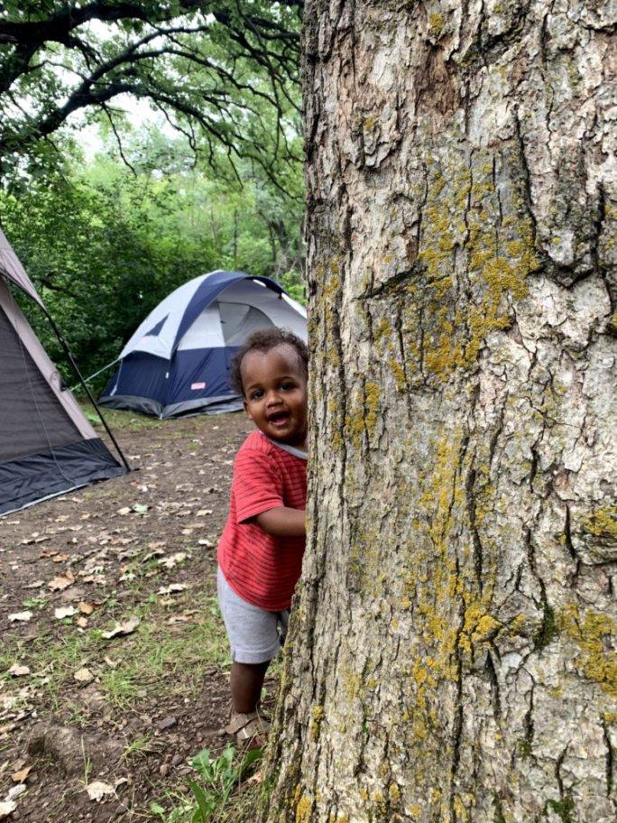 Toddler boy pokes his head around a tree