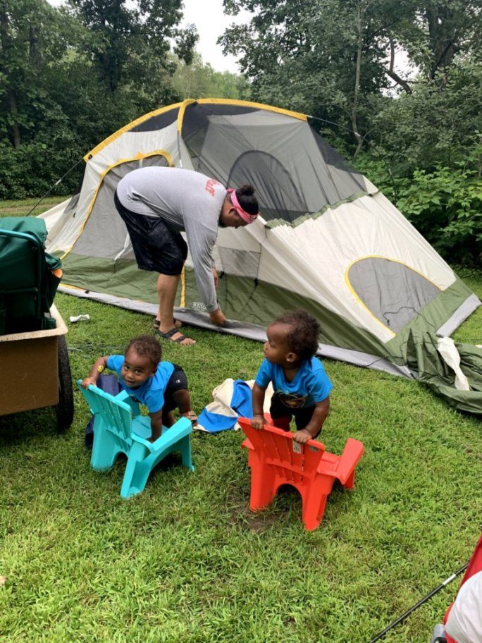 Father setting up tent while 2 toddlers watch