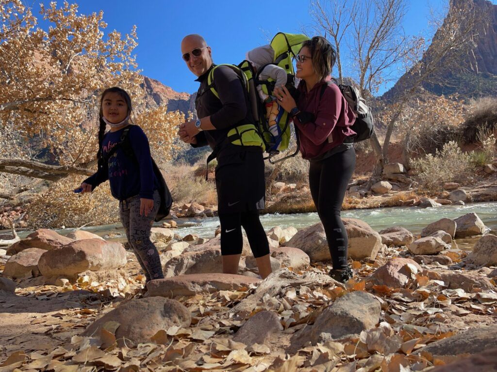 family hiking along a river