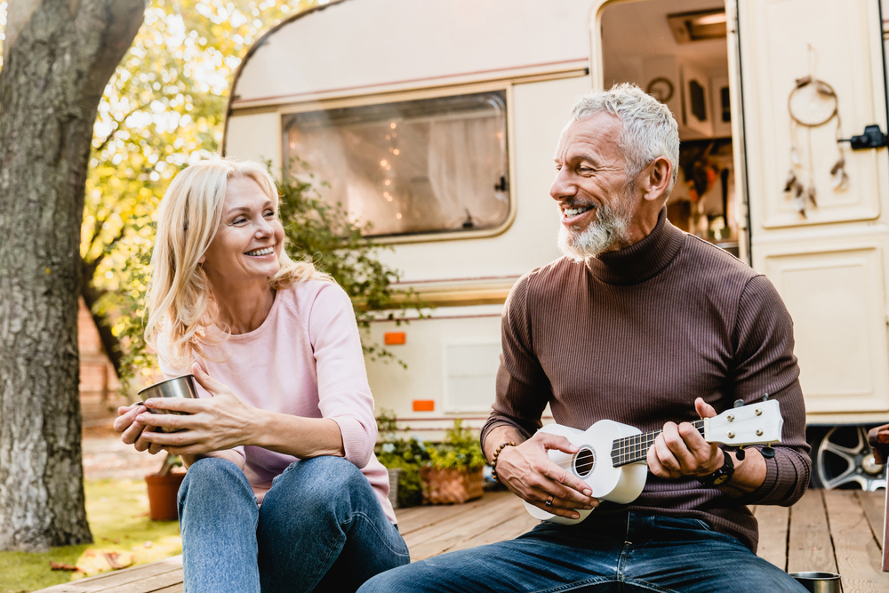 Mature man playing the ukulele for his wife near a campervan