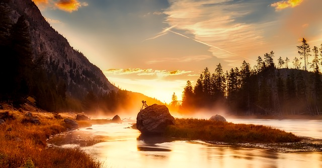 Yellowstone National Park at sunset with mist rising from a river