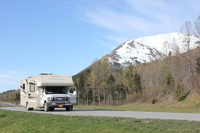 a Class C camper next to a snow-capped mountain