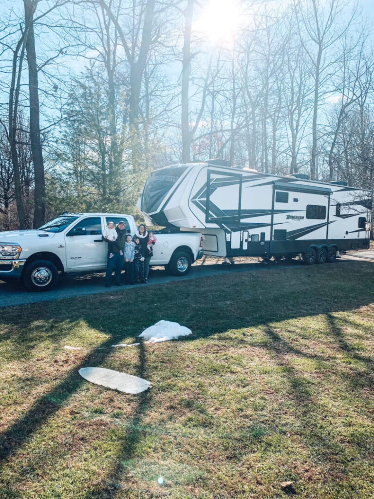 Family poses in front of fifth-wheel RV trailer and pick up truck