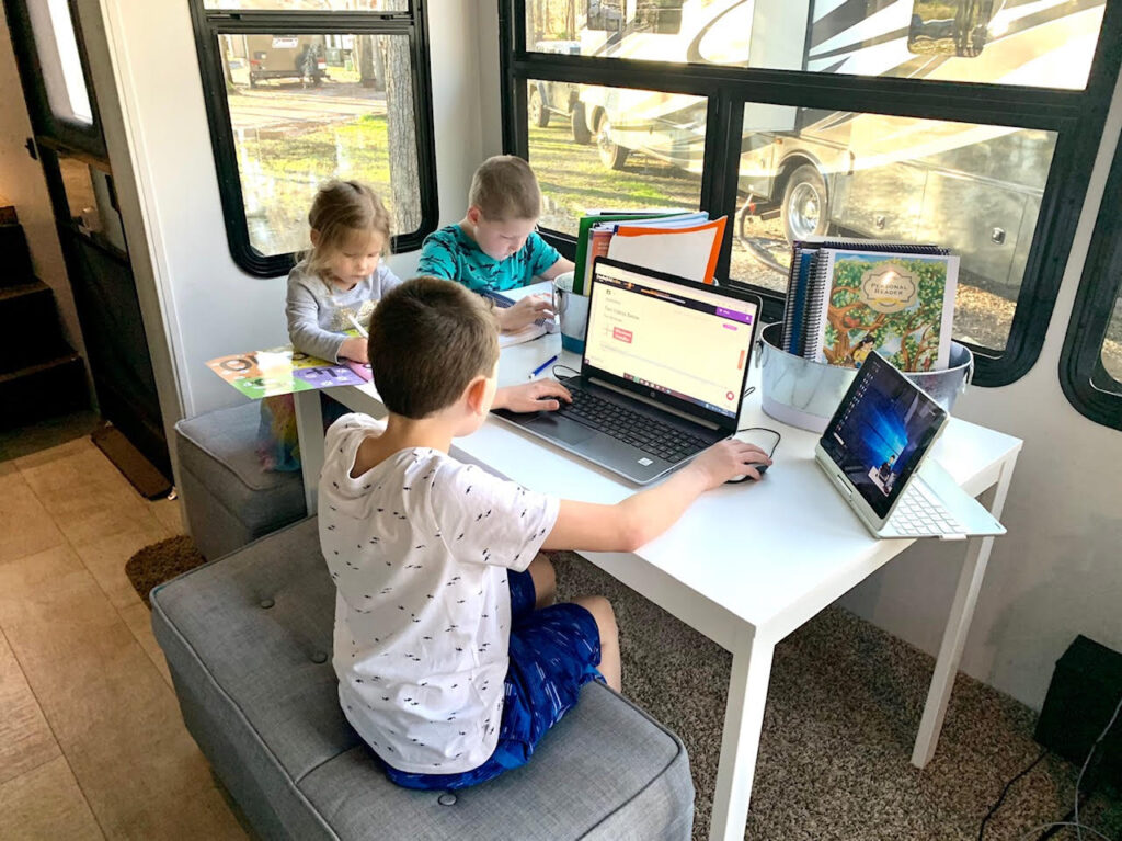 three children sit around a table on their computers during homeschool