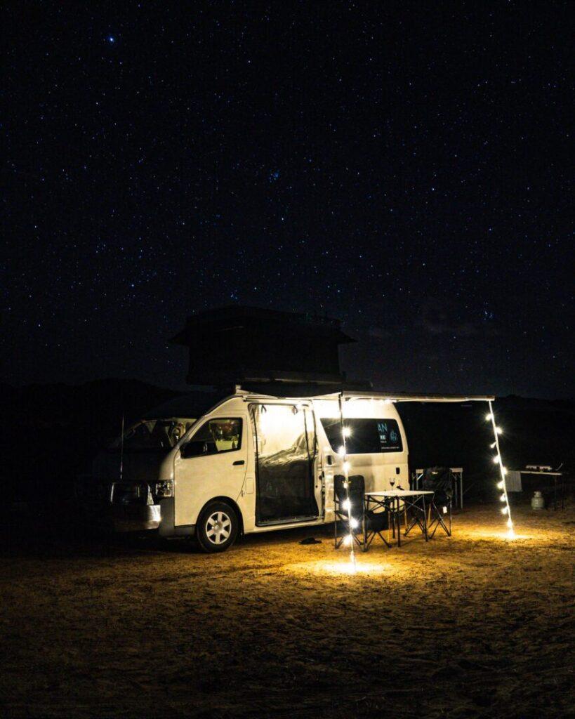 a camper van outlined in twinkle lights