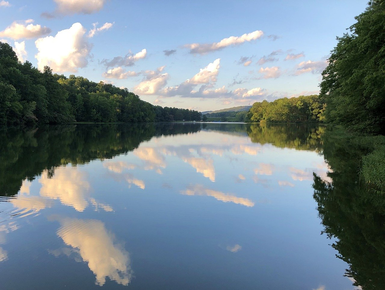 A shimmering lake reflects fluffy clouds at Oak Mountain State Park in Alabama.