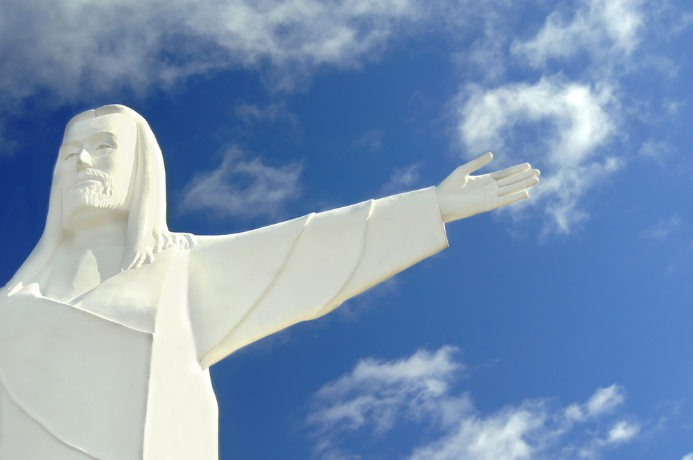 Christ of the Ozarks statue embraces the heavens. Christ's arms are outstretched toward blue sky and white clouds.