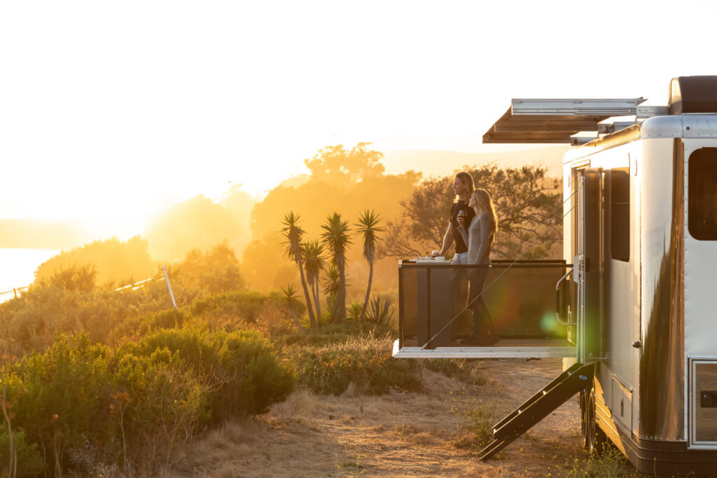 Couple stands on deck off the side of a travel trailer during sunset
