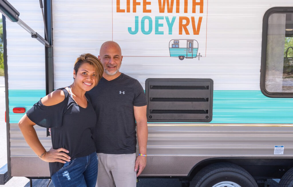 couple standing in front of their RV