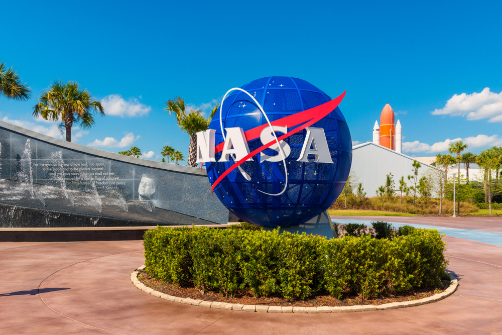 Cape Canaveral, FL, USA - April 1, 2015: NASA Logo on Globe at Kennedy Space Center Visitor Complex in Cape Canaveral, Florida, USA. To the left is a painting visible of President John F. Kennedy.