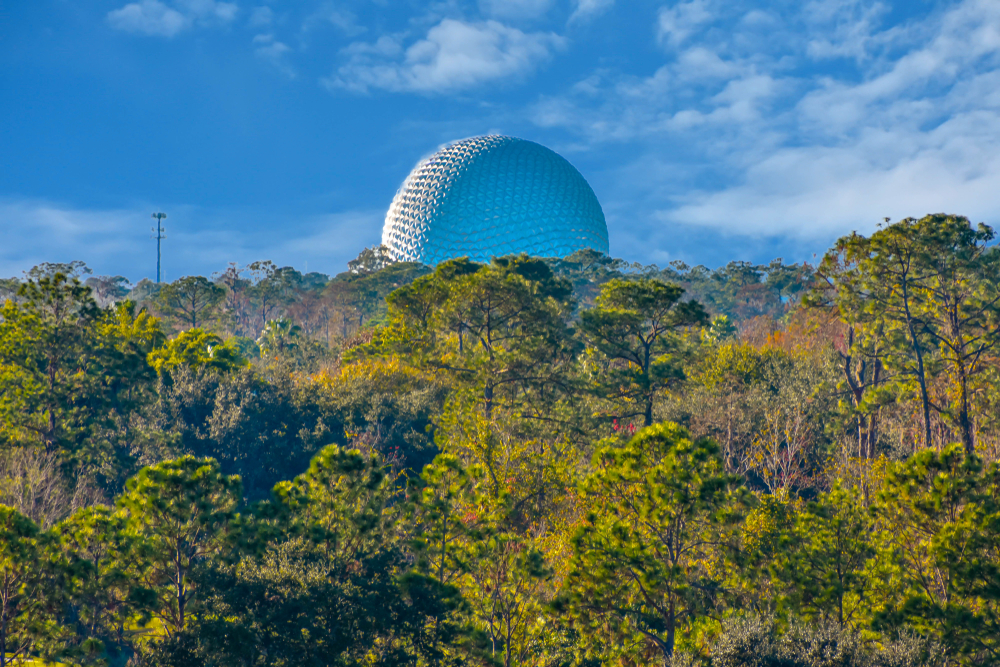 Orlando, Florida. January 12, 2019 Partial view of sphere and forest trees on light blue sky cloudy background at Lake Buena Vista area.