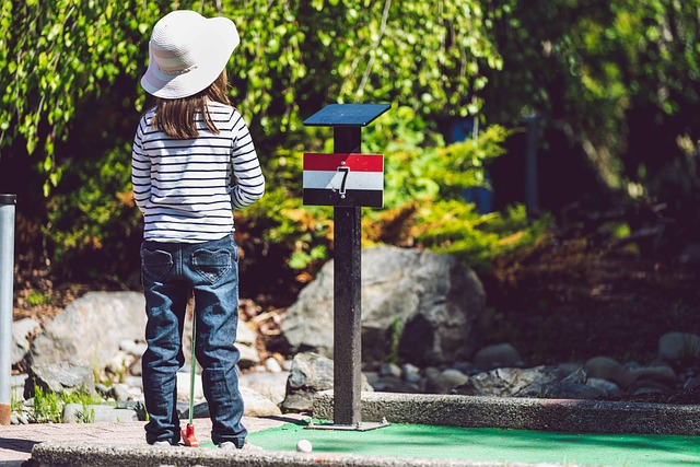 little girl in a sun hat playing mini golf