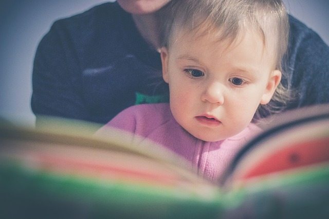 a baby and her parent reading a book