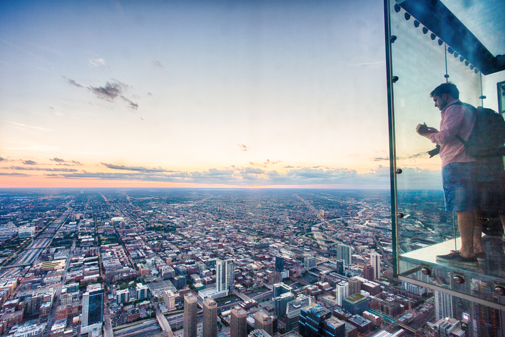 Chicago, Illinois, USA - June 2016: A tourist takes a picture of the Chicago skyline from one of the glass boxes of the Willis Tower Skydeck Ledge near sunset