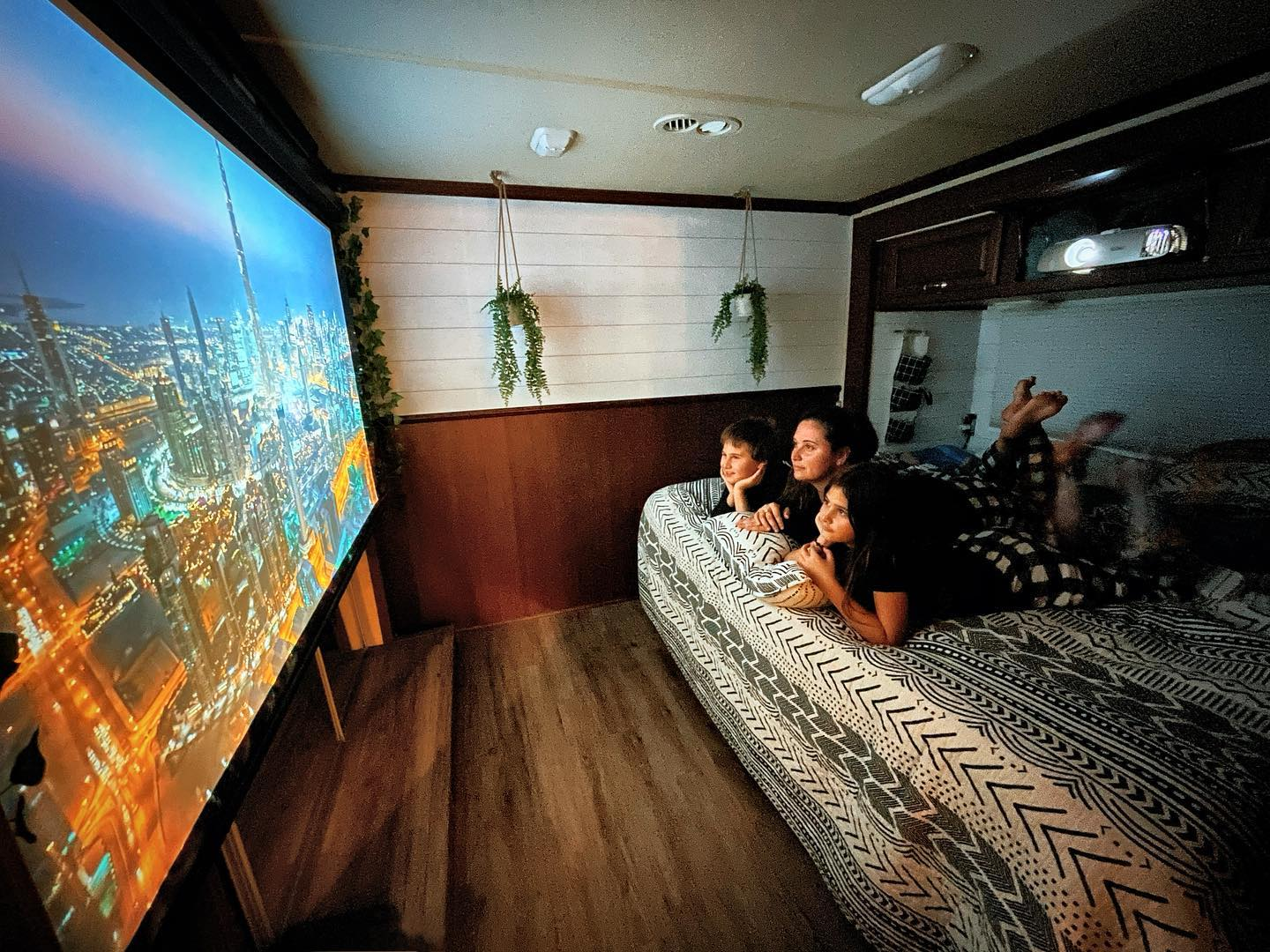 family using a projector to watch media in their RV
