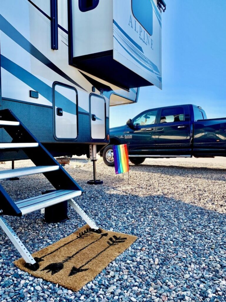 Exterior of a fifth-wheel trailer parked next to a truck with a rainbow pride flag