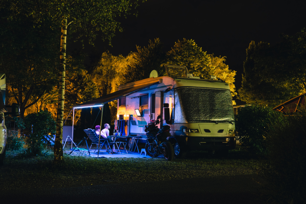 People sit under an awning of an RV and watch TV at night.