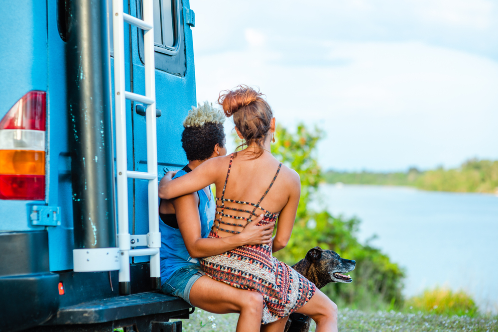 Couple sits on the back of their campervan with their dog by a lake