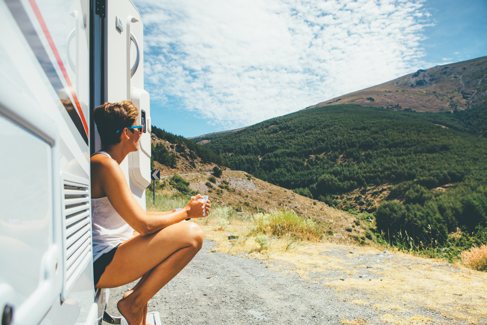 Young person sits on steps of RV and looks over a valley