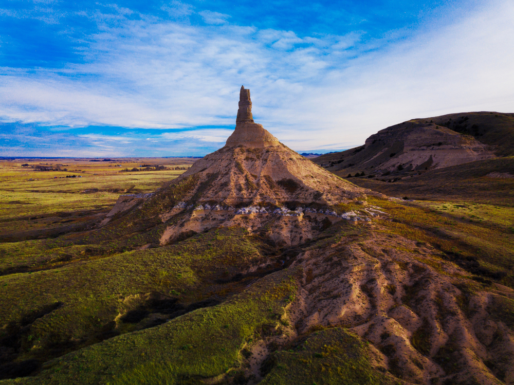 A tall, cone-shaped rock formation topped with a narrow rock tower sits next to a bluff and open fields.