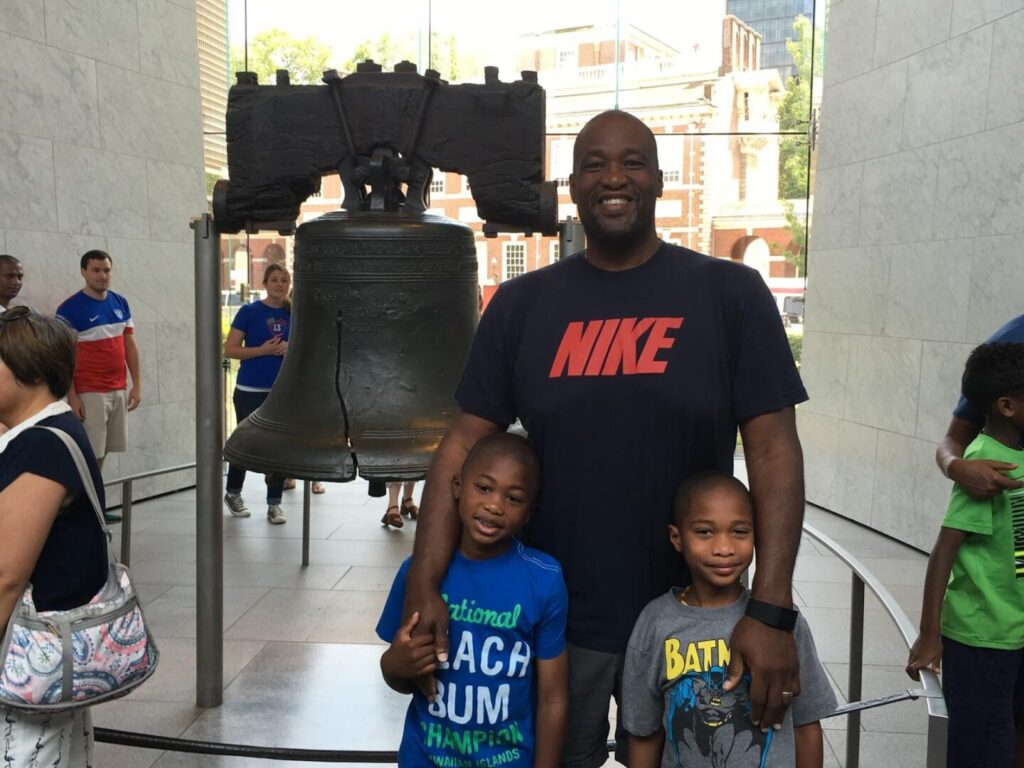 father and two sons smile at liberty bell in Philadelphia