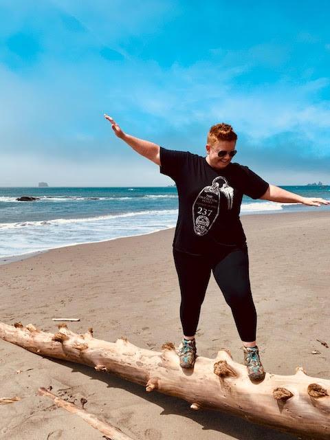 Woman balances on a log at Rialto Beach Olympic NP