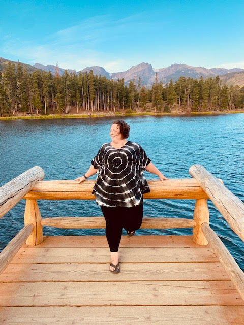 Woman stands on pier with Sprague Lake in Rocky National Park in background